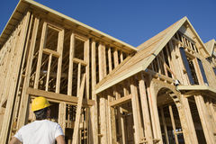 Worker Looking At An Unfinished Housing Frame Stock Image