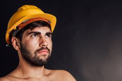 Worker looking up. Portrait of an undressed bearded worker looking up - isolated on black Royalty Free Stock Photos