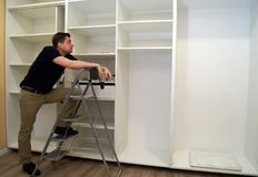 Worker looking at wardrobe. Cabinet assembly concept. A Worker looking at wardrobe. Cabinet assembly concept Stock Images