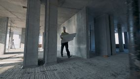 A man holds blueprint while walking in a building, close up. stock footage