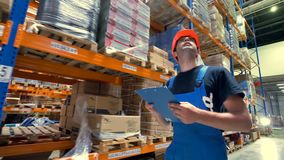 A worker in a hardhat and walks in a warehouse. stock footage
