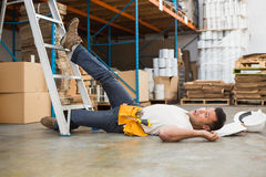 Worker lying on the floor in warehouse. Side view of male worker lying on the floor in warehouse Stock Images