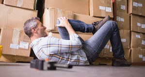 Worker lying on the floor in warehouse. Side view of male worker lying on the floor in warehouse Stock Photo