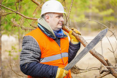Worker with machete working in forest Royalty Free Stock Image