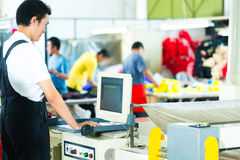 Worker on a machine in asian factory. Worker or production manager at a screen of a large machine in a textile factory in Asia Royalty Free Stock Image