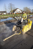 Worker with machine on asphalt road Stock Photo