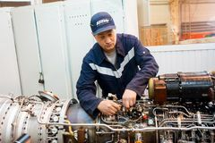 Worker maintaining helicopter engine. Tyumen. Tyumen, Russia - June 5, 2019: Aircraft repair helicopter UTair Engineering plant. Worker maintaining engine of Mi royalty free stock photos
