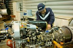 Worker maintaining helicopter engine. Tyumen. Tyumen, Russia - June 5, 2019: Aircraft repair helicopter UTair Engineering plant. Worker maintaining engine of Mi royalty free stock image