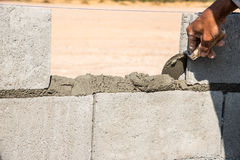 Worker make concrete wall by cement block and plaster at constru. Orker make concrete wall by cement block and plaster at construction site ,worker hand wearing royalty free stock photography