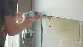 Worker make install drywall and using screwdriver and screw for work, closeup. Worker make install drywall and using screwdriver and screw for work at newly stock video footage