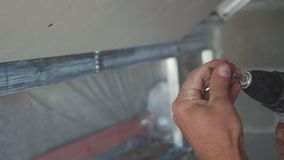 Worker make install drywall and using screwdriver and screw for work, closeup. Worker make install drywall and using screwdriver and screw for work at newly stock footage