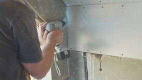 Worker make install drywall and using screwdriver and screw for work, closeup. Worker make install drywall and using screwdriver and screw for work at newly stock video