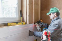 Construction worker thermally insulating eco wooden frame house Stock Photography