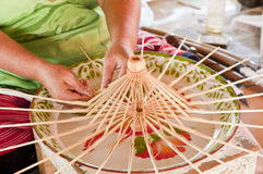 Worker making bamboo umbrella frame. Royalty Free Stock Images