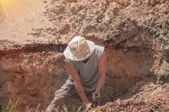 Worker male dig a hole to fix water leak at large on the road.  Stock Photo