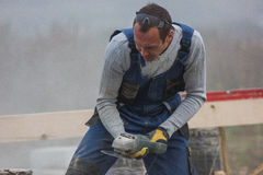 Worker man builder working with circular saw outdoors, sawdust flying around Stock Photo