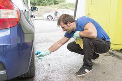 Worker man cleaning car. Stock Photo