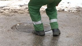 Worker man close drainage sewage well hole on street in winter