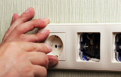 Worker man electrician is repairing damaged sockets in the apartment, installation of new  closeup Royalty Free Stock Images