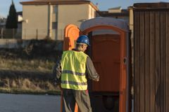 Worker man going to the bathroom portable. To make pee Stock Images