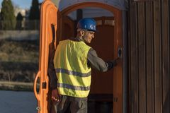 Worker man going to the bathroom portable. Smiling Stock Images