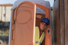Worker man going to the bathroom portable. Smiling with confusion, is woman toilet Stock Photography