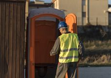 Worker man going to the bathroom portable. In sunset image Stock Photos