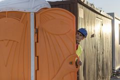 Worker man going to the bathroom portable. Looking out Stock Photos