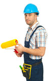 Worker man holding paint roller Stock Images