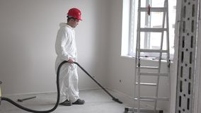 Worker man hoovering construction works remains and dust with vacuum cleaner stock video footage