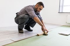 Worker Man laying laminate flooring in construction concept. Man laying laminate flooring in construction concept Royalty Free Stock Images