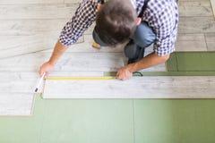 Worker Man laying laminate flooring at home room. Man work laying laminate flooring at home Stock Photography