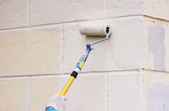 Worker man painter paints the wall with beige paint  a roller. Royalty Free Stock Photo