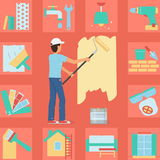 Worker man painting wall with a roller Royalty Free Stock Image