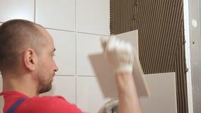 Worker man put plate on wall repairing in bathroom indoors stock footage