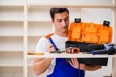 The worker man repairing assembling bookshelf Stock Photography