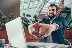 Worker man exercising stretching arms in office. Stock Images