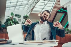 Worker man exercising stretching arms in office. Stock Photography