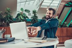 Worker man exercising stretching arms in office. Royalty Free Stock Photo
