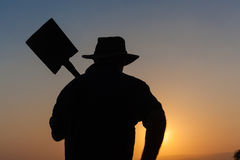 Man Outline Spade Sunset Silhouette. Worker mans body outline with shovel spade at sunset silhouette Stock Image