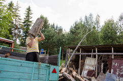 Worker man unload tree logs firewood from trailer Stock Image