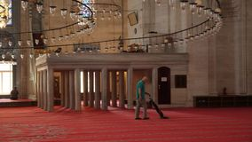 Worker man vacuuming the red carpet in a big. Turkey, Istanbul - 5 June 2019: worker man vacuuming the red carpet in a big in the structure of the Suleymaniye stock footage
