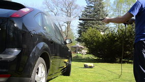 Worker man wash car automobile with strong water jet in summer stock footage