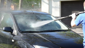 Worker man wash car windscreen with strong pressure water jet Royalty Free Stock Photos