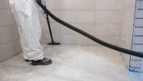 Worker man in white overall clean construction remains and dust vacuum cleaner stock video