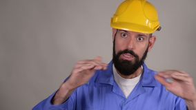 Worker man in yellow helmet explain something and show ok gesture on grey background. Portrait of young worker in yellow helmet explain something and show ok stock video
