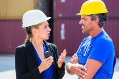 Worker and Manager on container terminal of port. Discussing Royalty Free Stock Image