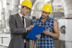 Worker with manager discussing over clipboard in industry Royalty Free Stock Photo