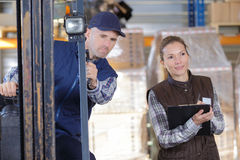 Worker and manager distributing goods in warehouse. Worker and manager distributing goods in a warehouse Stock Photo