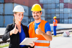 Worker and Manager of freight forwarding company. Manager with clipboard full of freight documents and worker on shipment yard in giving thumbs-up stock photography